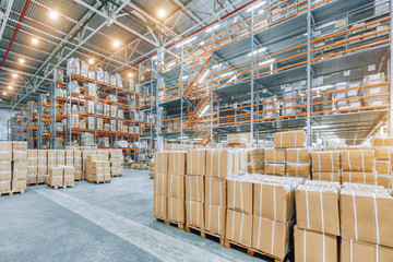 Large industrial warehouse with high racks. In the foreground are a lot of cardboard boxes.