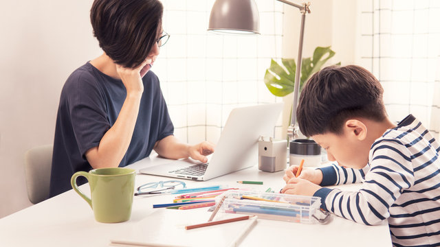 Social distancing & Work from home, Homeschool Asian little boy draw and color while stressed mother on phone, look at computer laptop working during pandemic of Covid-19, quarantine and city lockdown