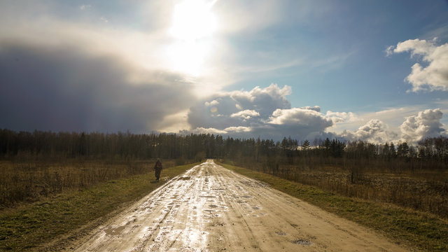 Cloudy sky after heavy rain and a country road shining under the sun