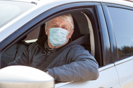 Senior man a driver using surgical mask to prevent virus infection, taxi driver