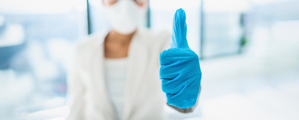 Coronavirus success happy news lab researcher doing thumbs up with medical gloves for vaccine. PPE for COVID-19 healthcare banner panoramic.