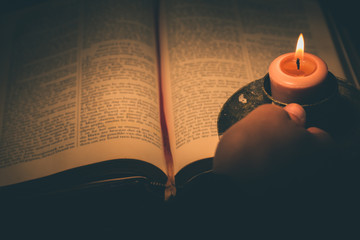 Fototapeta Cropped Hand Holding Illuminated Candle By Book obraz