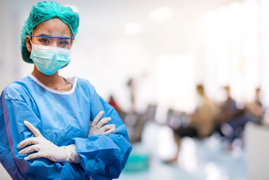 Doctors or surgeons wearing surgical mask with blur patient crowd background in hospital , during coronavirus or covid-19 crisis, medical concept.