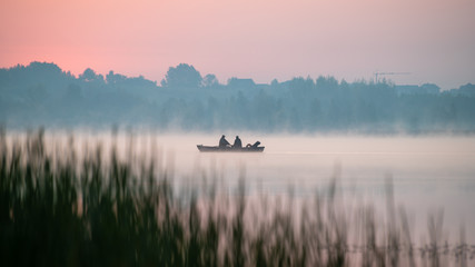 Ingelijste posters Lichtroze Wędkarze wiosłują łodzią przez jezioro w Świerklańcu.