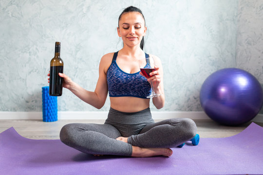 Young woman in sport outfit  doing fitness exercise with dumbbell and drinking glass of red wine, sitting on fitness ball at home