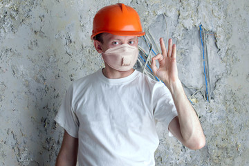 Man in protective mask and helmet on stucco wall background