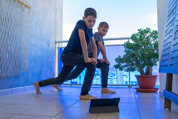 Boys with tablet computer doing sport exercises on balcony. Sport, healhty lifestyle, active leisure at home
