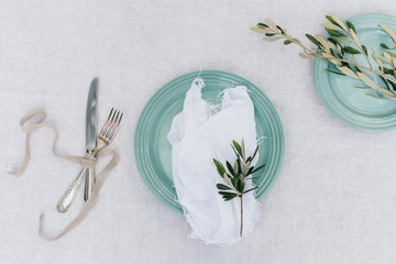 teal mint plate setting with olive branch on linen