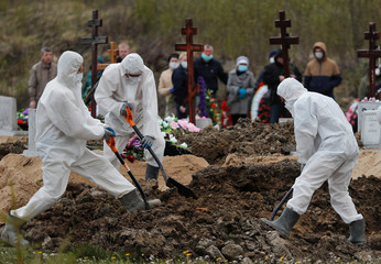Grave diggers bury a coronavirus disease victim in Saint Petersburg