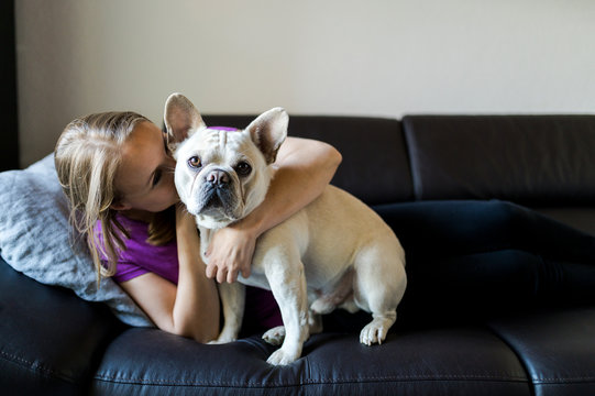 Woman is sitting with french bulldog on couch
