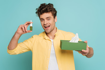 Front view of man smiling and showing bottle with nasal drops and box with napkins isolated on blue