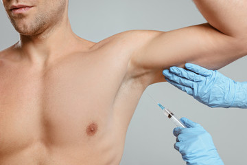 Cropped view of doctor doing botox injection from hyperhidrosis to man isolated on grey