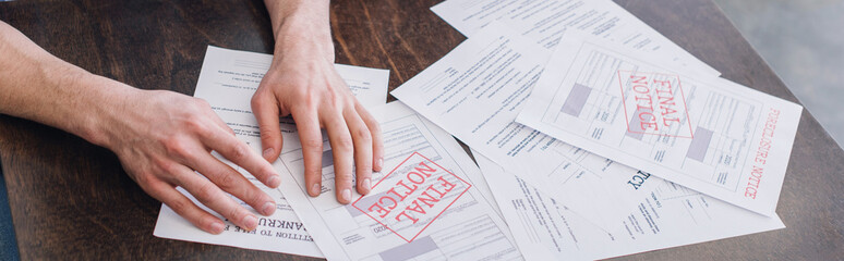 Cropped view of male hands near documents with foreclosure and final notice lettering on table,...