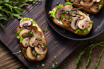 Sandwich with mushrooms and cream cheese on a rustic wooden background.