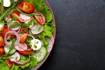 Healthy fresh salad with radish, cucumber, cherry tomato and mozzarella on a dark color background. The concept of a delicious and healthy diet.