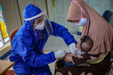 A medical staff member wearing PPE vaccinates a baby in Tangerang, near Jakarta