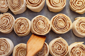 cooking home cinnabon buns from yeast dough on in row baking paper lie in a row and wooden spatula close up
