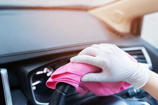 car wash,  worker hand wear white glove cleaning console steering wheel with microfiber cloth pink. hygiene prevention  antibacterial of corona virus outbreak.