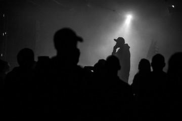A silhouette of singer rap musician during live concert in dark light. Dark background, smoke, spotlights