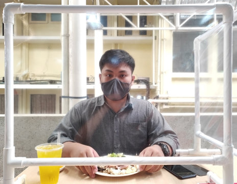 Front view on men wearing masks were eating lunch at a restaurant partition for prevent airborne contamination in a viral epidemic situation  - Social Distancing and New normal concept.