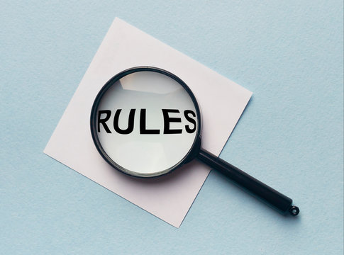 Magnifying glass or loupe with the word rules on a white memo note on blue background. Searching new rules