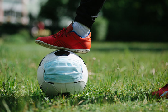 Foot and shoe with soccer football with face mask for sports during covid-19 pandemic