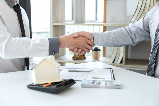 Real estate agent are shaking hands after good deal and giving house, keys to customer after signing contract to buy house with approved property application form