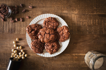 Chocolate homemade cookies with macadamia nuts cocoa beans and sugar in a rustic atmosphere