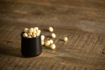 Macadamia nuts in a rustic black jar on a wooden table
