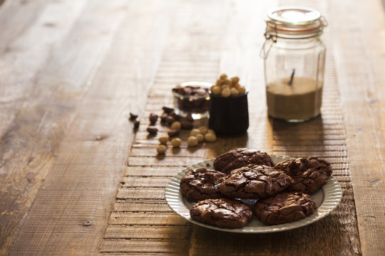 Homemade chocolate and macadamia nuts cookies in a rustic environment with cocoa beans and sugar