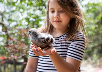 A child holds a baby chicken outdoors
