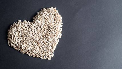 Heart shape of sunflower seeds on black background with copy space. Heap of sunflower seeds in the shape of a heart