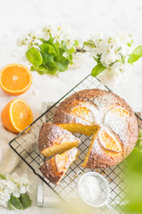 Round cupcake with orange with icing sugar on a wire rack with a cut piece of cake with flowers on a gray background vertical arrangement
