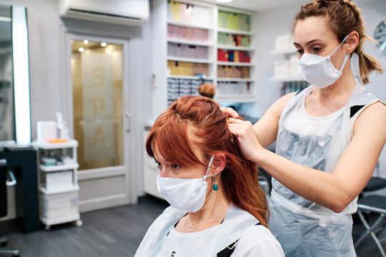 hairdresser in beauty salon with face mask to protect from coronavirus epidemic - social distancing concept