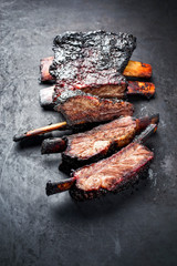 Barbecue burnt chuck beef ribs marinated with hot chili sauce as closeup on an old rustic board