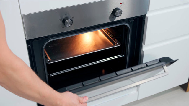 Opening Oven in white kitchen witk light.