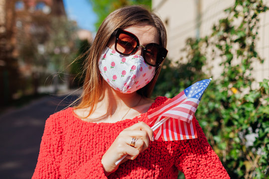 USA Independence day. Woman wears protective mask outdoors holds flags during coronavirus covid-19 pandemic.