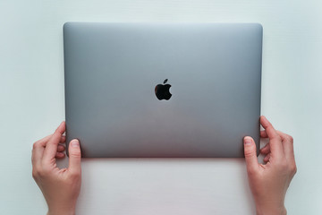 Batumi, Georgia - May 04, 2020. Macbook Pro 16 inch model of space gray color of Apple brand in hands on a white background released in 2019