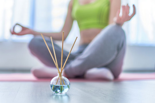 Fitness woman in lotus pose with aroma sticks and essential oil bottle during yoga training, aromatherapy treatments and meditation. Mental health
