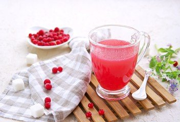 Traditional Russian hot drink red currant jelly or kissel in a transparent glass cup on a light concrete background. Drink recipes. Berry drinks.