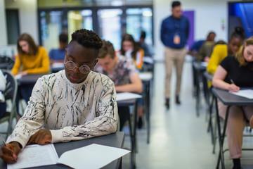 Focused high school boy student taking exam at desk