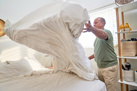 Man with duvet making bed in bedroom