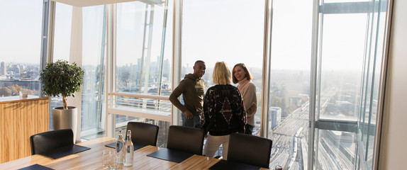 Business people talking at sunny highrise office window
