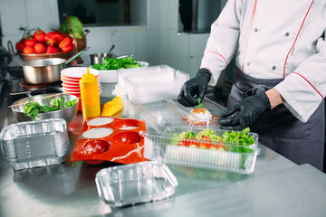 Food delivery in the restaurant. The chef prepares food in the restaurant and packs it in...