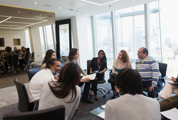 Business people talking in circle in conference room meeting