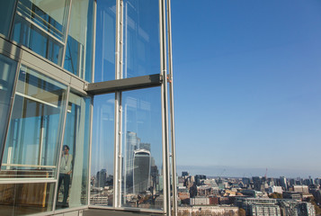 Businessman using smart phone at sunny highrise office window