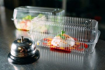 food delivery. distribution table in a restaurant with a metal bell. food in plastic containers....