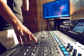Male producer at music sound board in recording studio