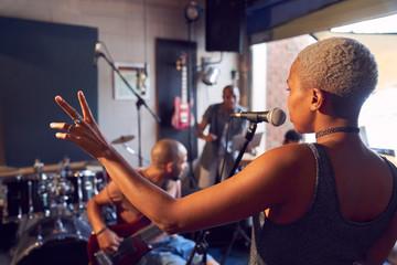 Female musician singing into microphone in garage recording studio Fotobehang