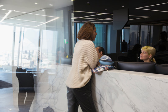 Businesswoman talking with receptionist in office lobby